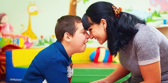 Verzorger houdt handen vast van verstandelijk gehandicapt kindje