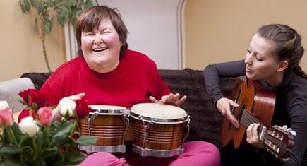 Verzorger speelt muziek samen met een verstandelijk gehandicapte vrouw