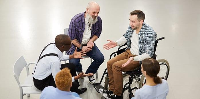 Een groep mensen, waarvan er eentje in een rolstoel zit, houden een kringgesprek
