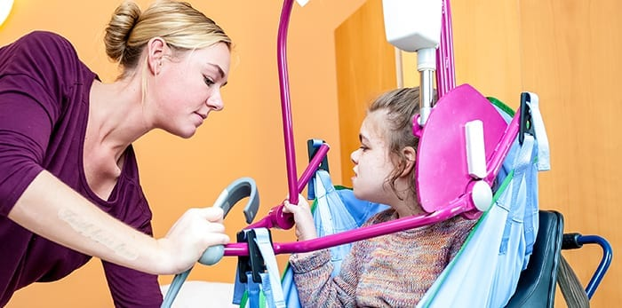 Verzorger helpt jong gehandicapt kindje